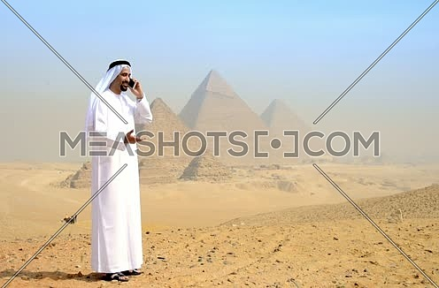 Emiratie man at the pyramids talking on the phone