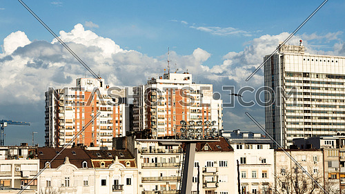 Urban old buildings with white fluffy clouds on the blue sky