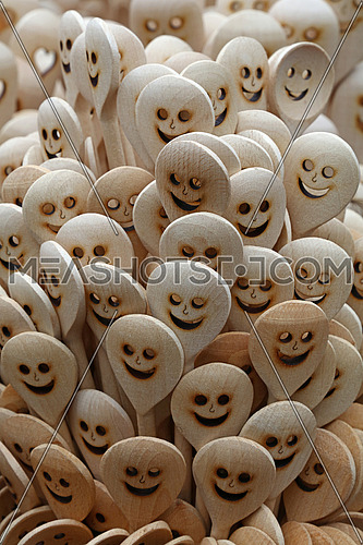 Close up handmade rustic wooden cooking spoons with carved happy smiling face icons in retail market stall display