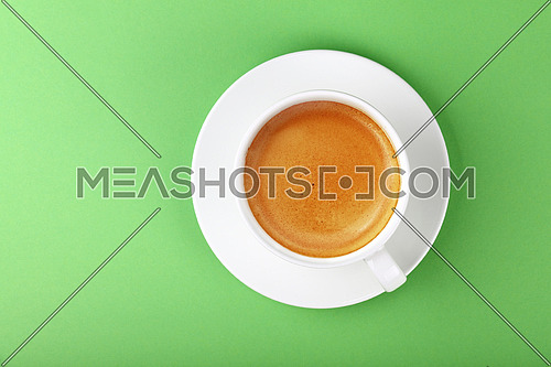 Close up one full white cup of espresso coffee and saucer over pastel green paper background, elevated top view, directly above