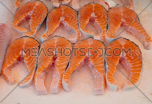 Close up several fresh raw salmon fish steaks on ice at retail display of fisherman market, high angle view