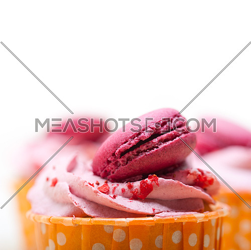 fresh pink berry cream cupcake with macaroon on top over rustic wood table