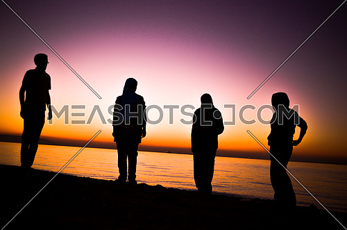 a group of four friends standing by the beach at sunset