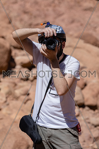 Portrait for a photographer taking shots Sinai Mountain from wadi Freij at day.