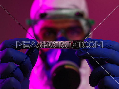 Coronavirus, Doctor holding positive covid-19 virus Blood Sample tube. Wearing biohazard epidemic Protective mask, suit and glows.