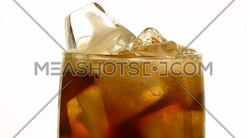Extreme close up of pouring carbonated cola soft drink in transparent glass with ice cubes until full over white background, low angle side view, slow