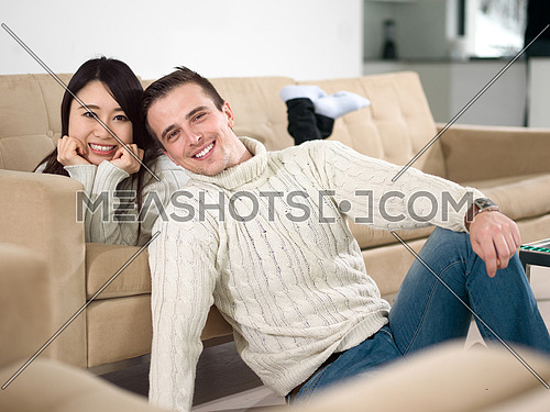 Young multiethnic couple relaxing on the sofa at luxury living room