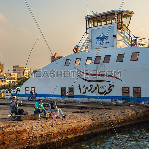 Port Fuad, Egypt - November 10, 2018: Local citizens of Port Fuad district fishing beside Port Said ferry boat at Suez Canal