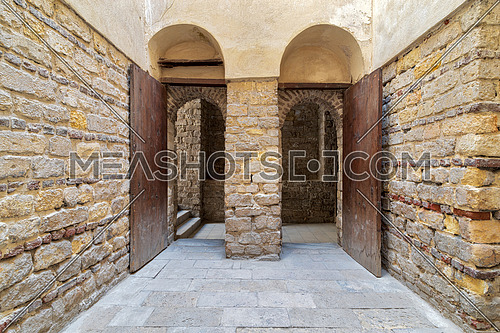 Exterior brick stone passage with two adjacent vaulted opened wooden grunge doors, Sultan Qalawun Complex, Cairo, Egypt