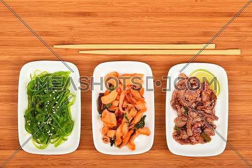 Three portions of seafood marinated salad with octopus cuttlefish, squid and seaweeds in small white plates with chopsticks on bamboo wood, top view