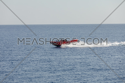 Long shot for speed-boat sailing fast in The Red Sea by day.