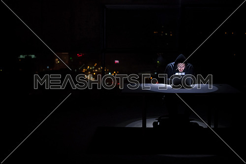 Young talented hacker using laptop computer while working in dark office with big city lights in the background at night