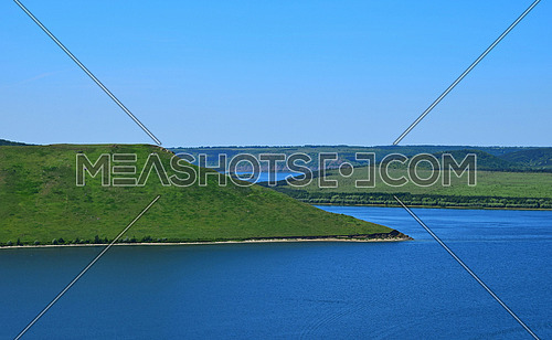 Beautiful vivid riverside landscape with high river banks, green hills, blue sky and rippled water in day time
