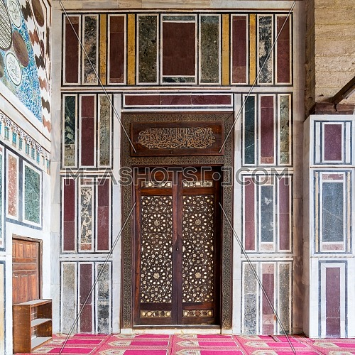 Old colorful marble wall with wooden door decorated with arabesque ornaments in public historic Al Moaayad Mosque, Cairo, Egypt