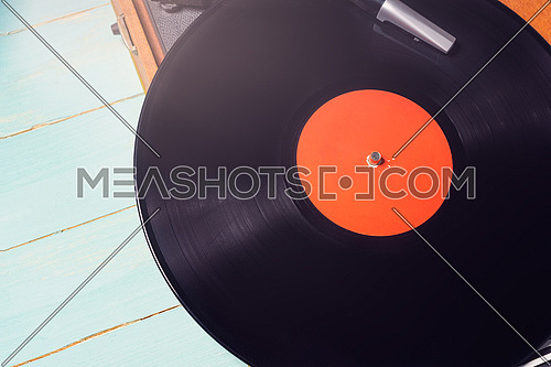 Old gramophone with a vinyl record on green wooden table, top view.