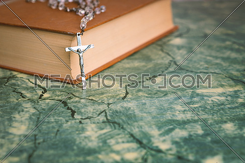 Silver rosary and cross resting on the closed book at green table,front view.religion school concept.Vintage style.