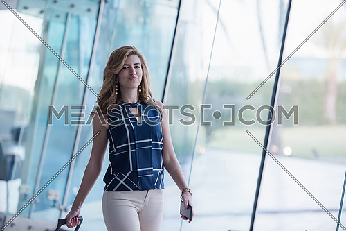 attractive middle eastern business woman portrait with travel bag at airport terminal