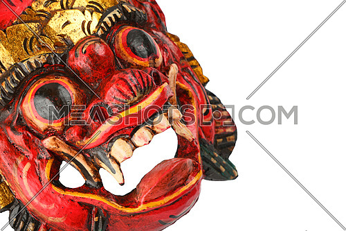 Asian traditional wooden carved painted red mask with face of human or demon isolated on white background,  crop