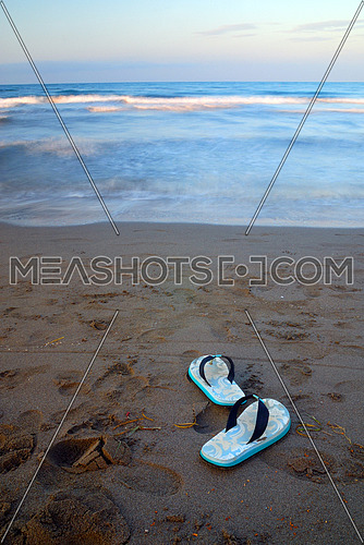 sandals on beach at early mornig with long exposure