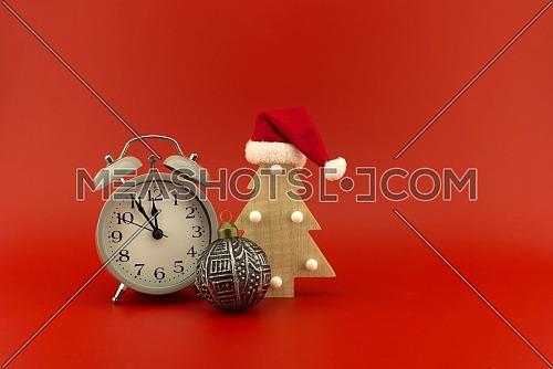 Christmas tree with red Santa hat and vintage alarm clock on a festive red background with copy space for text . New Year and Christmas holiday season concept card decoration