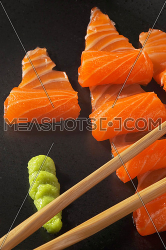 slice of salmon sushi with wasabi sauce