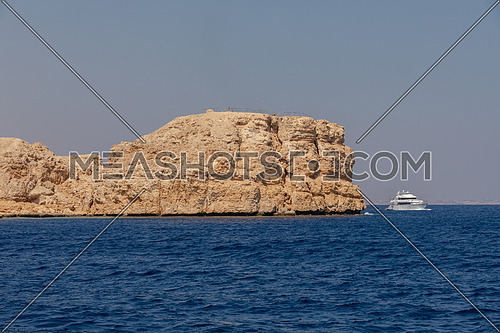 Long shot from Red Sea showing Ras Muhammed Island and a yacht by day