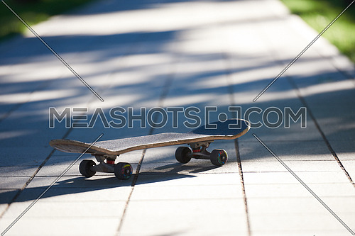 Old used skateboard isolated on the ground on street