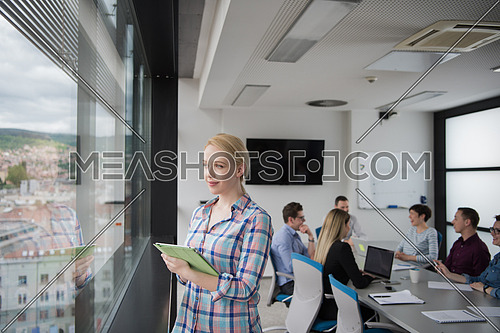 Business Woman Using Digital Tablet in corporate office by window