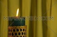 Teal candle with straw twigged holder trembling flame close up out of the yellow folded fabric cloth background, off-center, blown out