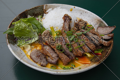 Close up portion of sliced roasted crispy Peking duck curry with rice and salad on plate over table, high angle view