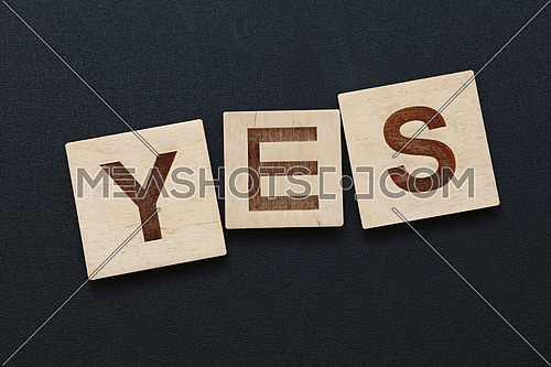 Close up word YES on wooden scrabble letter signs over black board background