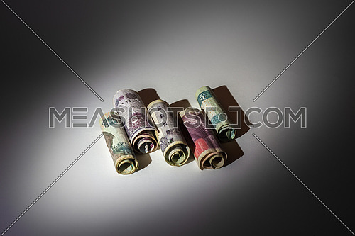 Egyptian Money rolled under a spot light in a grey background