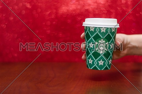 Starbucks takeaway paper cup, in special design for Christmas on a festive red background; December 2018 - Cairo, Egypt