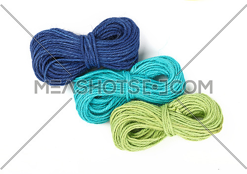 Group of three small coil skeins of natural colorful multicolor jute twine rope, green, blue and teal, isolated on white background, close up, elevated top view, high angle