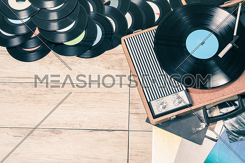Gramophone with a vinyl records on wooden table, top view and copy space,photo desaturate and split toning for old style.