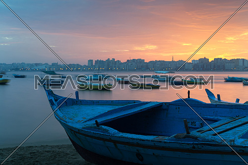 Turquoise blue fishing boat on the beach at sunrise with Alexandria skyline in far distance and colorful sky at sunrise