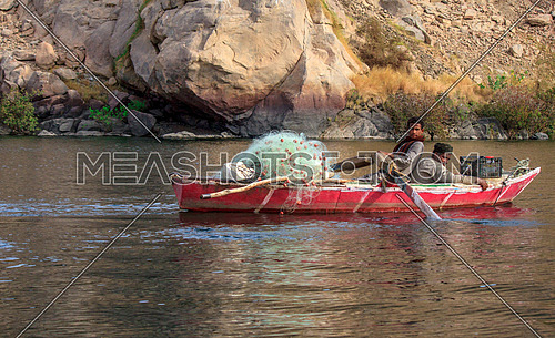 two fishermen in a rowing fishing boat in the river nile