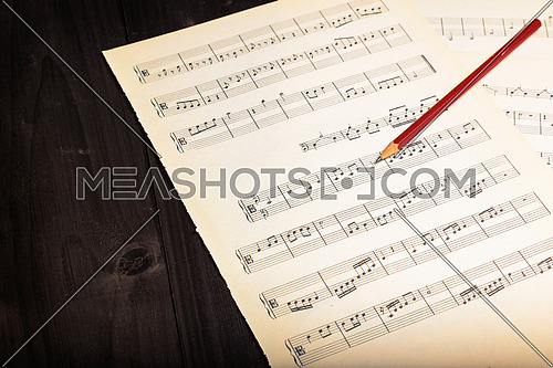 In the picture aged pages of sheet music, pencil  and wooden background,used split tonig for old/vintage style.