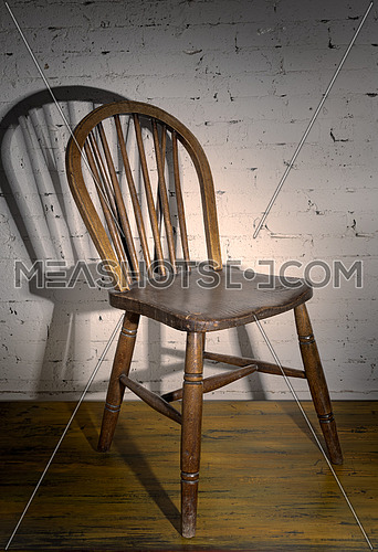 Still Life of  one vintage chair, wooden floor and white bricks wall, with strong shadow  in Studio