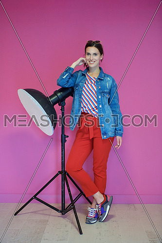 Young woman leaning against studio flashlight over a pink background. Female model wearing fashionable and casual clothes standing and looking to the camera. Photography professional equipment