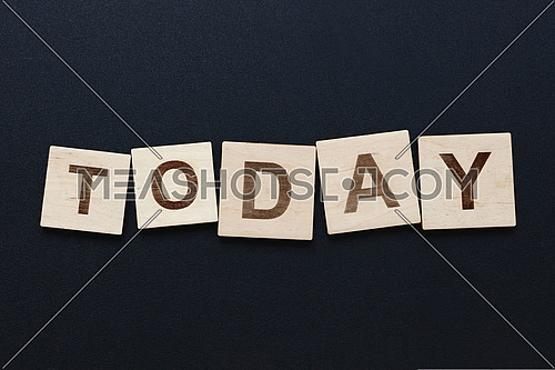 Close up word TODAY on wooden scrabble letter signs over black board background