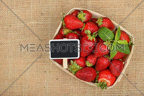 Wicker wooden basket of strawberries with mint leaves and chalk blackboard price tag sign on jute burlap canvas background, top view