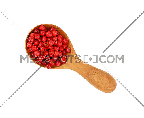 Close up one wooden scoop spoon full of red pink pepper peppercorns isolated on white background, elevated top view, directly above