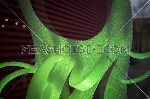 Close-up of green abstract stripes of foamy material on dark background