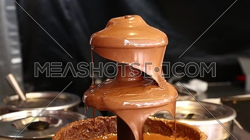 Close up of Belgian liquid milk chocolate fountain for sweet fondue dip desserts, low angle view