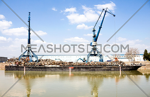 Cranes operating in the recycling area while reflecting out of water