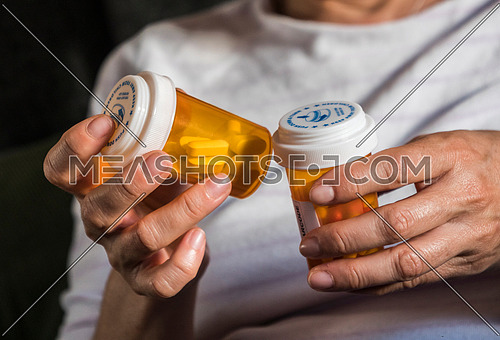 Woman examining medication treatment, several boats in the hand, conceptual image