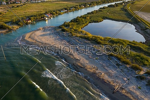 beautiful landscapes of the valleys near Ravenna ,Fiumi Uniti, where the river flows into the sea with the typical fishermen's huts at sunset