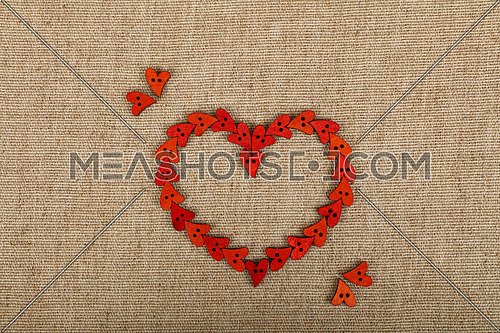 Red heart shaped handmade wooden sewing buttons on linen canvas, elevated top view, close up