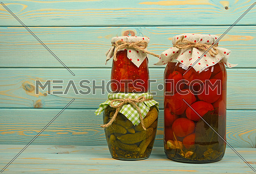 Close up of three glass jars of rustic homemade pickles, gherkin cucumbers, tomatoes and pepper salad, with linen textile top lid decorations and jute twine bows over vintage blue wooden planks, low angle side view